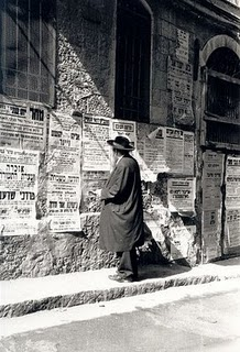 Jewish man looks at wall posters in Jerusalem